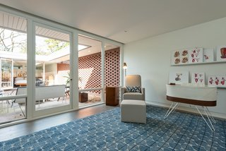 """A charming nursery looks onto the inviting courtyard. Custom """"midcentury vascular anatomy"""" artwork by owner Andre Uflacker, a radiologist and painter, adorns the space."""