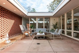 The interior courtyard is one of the best rooms in the house, embracing daylight and shadows.  Originally designed to hold a tree at the center, the courtyard now includes a fire pit.
