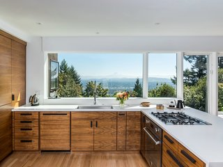 A large picture window provides endless views of the Cascade Mountains from this contemporary, open kitchen.