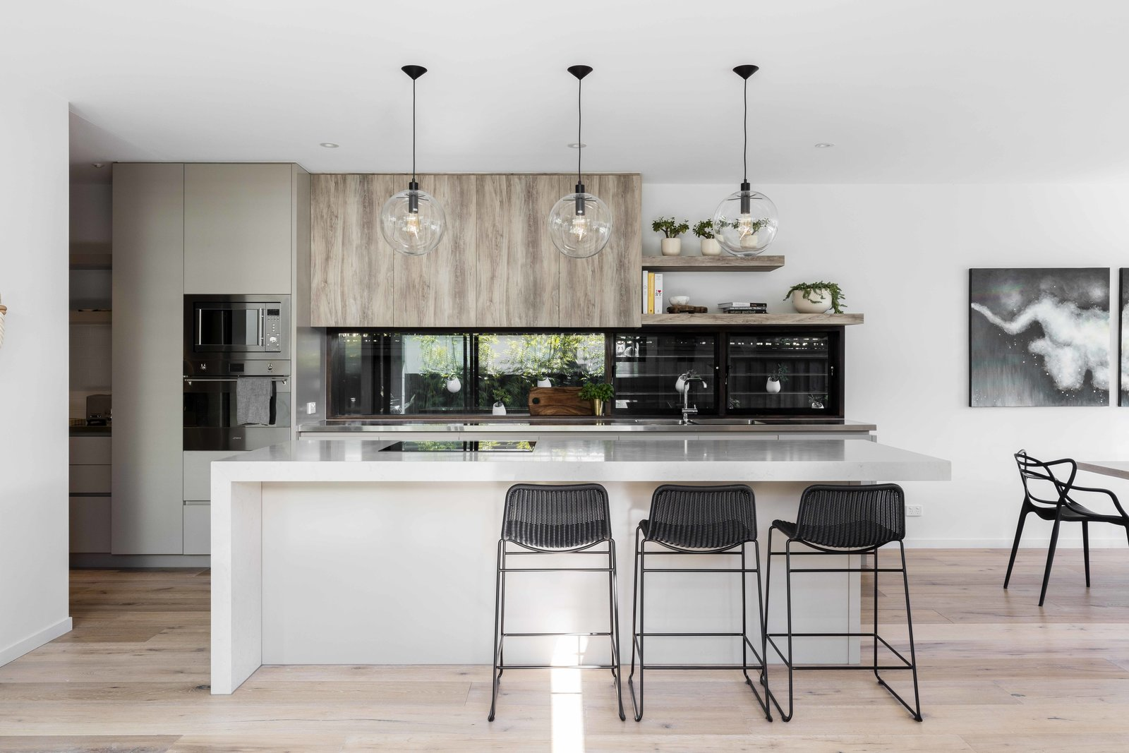 Kitchen, Stone Counter, Wood Cabinet, Light Hardwood Floor, Ceiling Lighting, Pendant Lighting, Range Hood, and Wall Oven  The Rose Bay House by Prebuilt