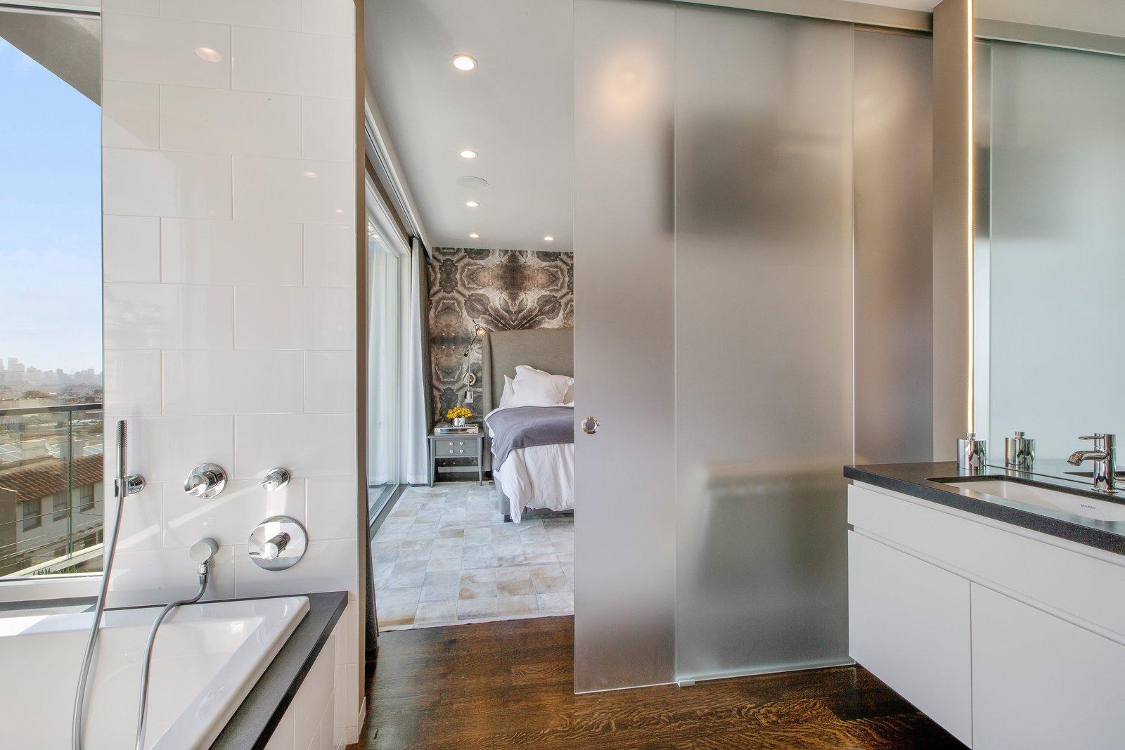 Bath Room, Granite Counter, Drop In Tub, Medium Hardwood Floor, Ceiling Lighting, and Undermount Sink  LEED Platinum House in SF by DNM Architecture