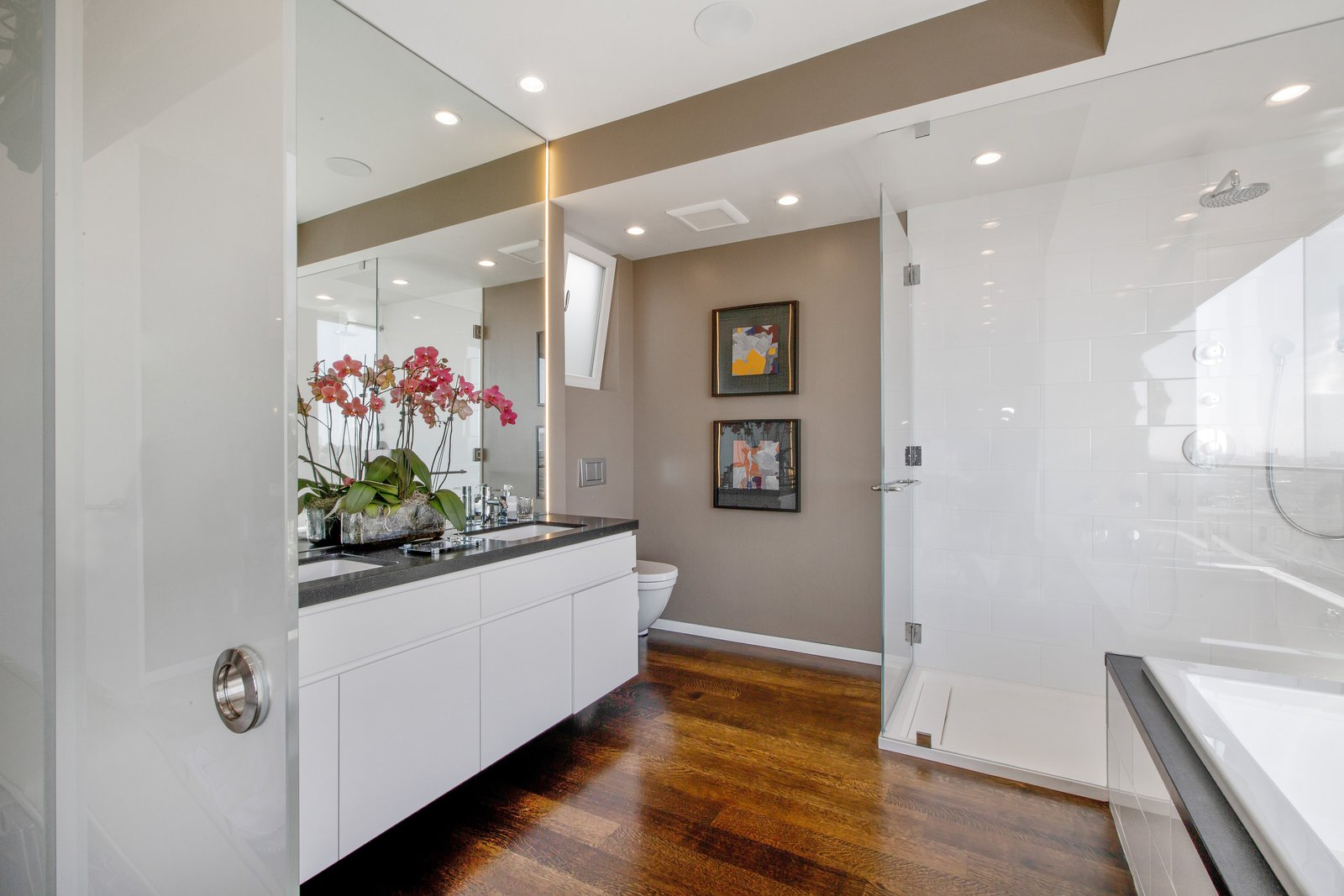 Bath Room, Granite Counter, Undermount Sink, Medium Hardwood Floor, Enclosed Shower, Full Shower, Drop In Tub, Ceiling Lighting, and One Piece Toilet  LEED Platinum House in SF by DNM Architecture