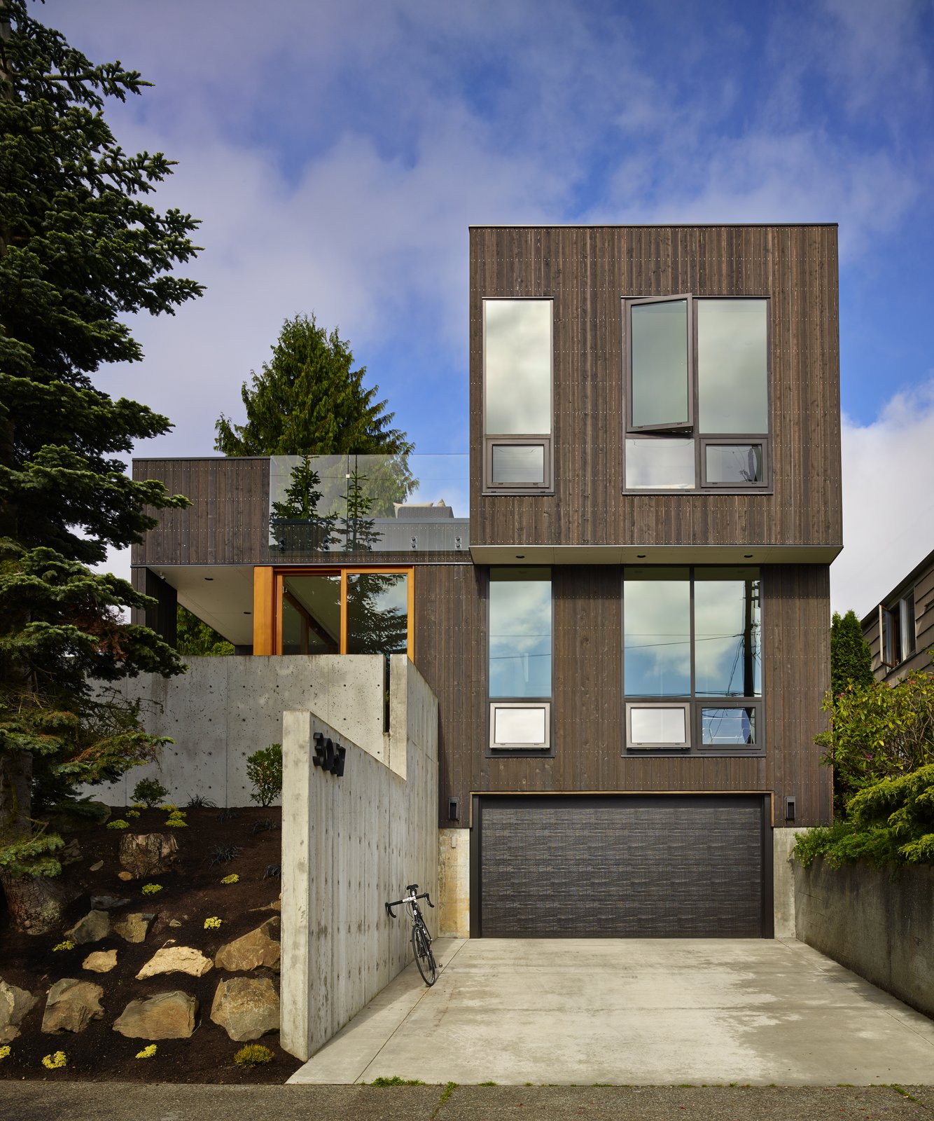 Tagged: Rooftop, Front Yard, Attached Garage, Casement Window Type, Exterior, Boulders, Trees, Hardscapes, Concrete Patio, Porch, Deck, Exterior, House, Concrete Siding Material, and Wood Siding Material.  BLK_LAB by Patano Studio Architecure