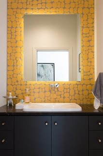 This bright bathroom features Rox Solar yellow ceramic tile by Modwalls Rex Ray Studio, which provides a pop of color, a bit of texture, and a dose of fun.