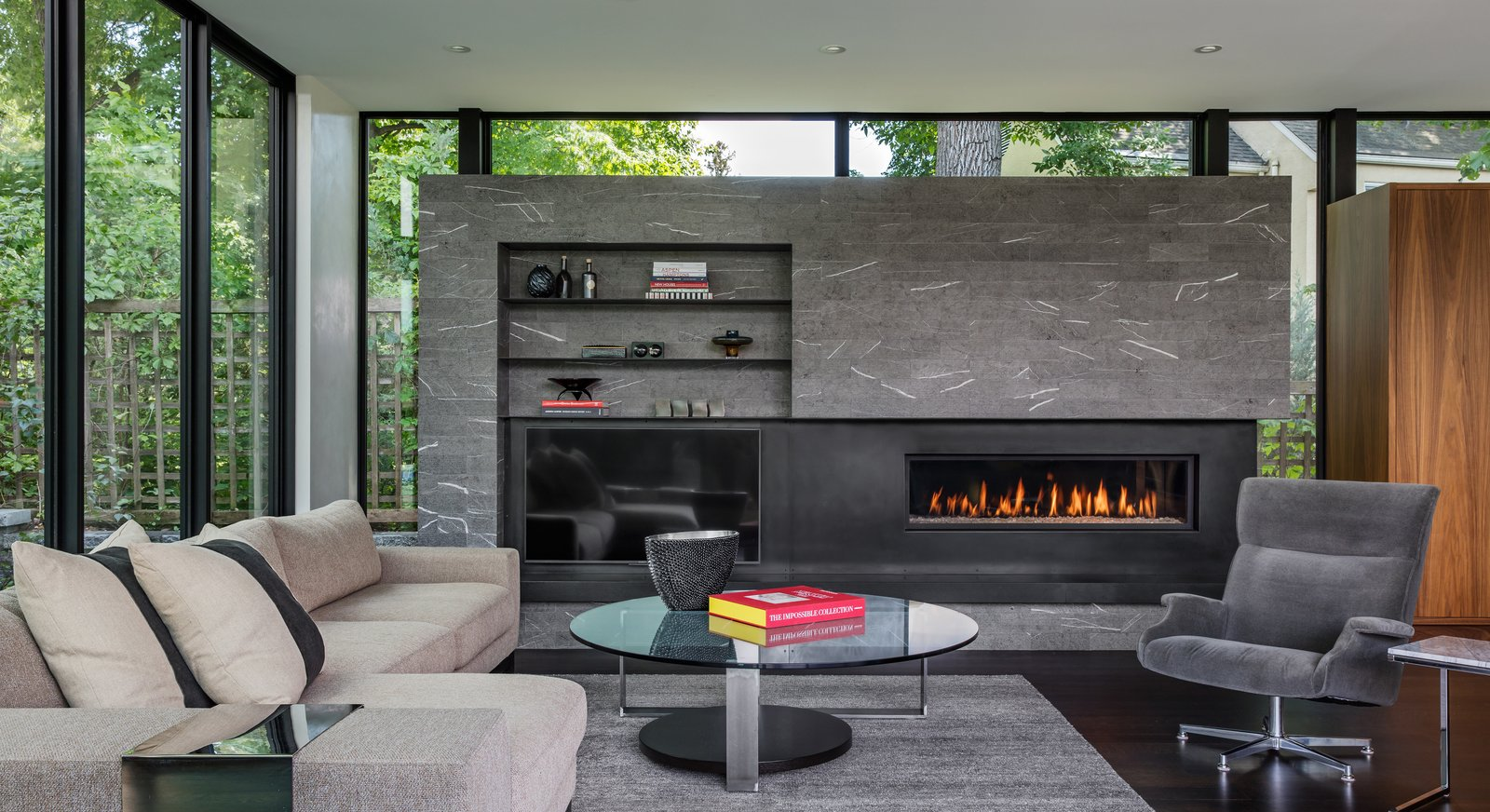 Living Room, Ribbon Fireplace, Corner Fireplace, Coffee Tables, Gas Burning Fireplace, Sectional, Bookcase, Recliner, and Dark Hardwood Floor  Calhoun Pavilions Residence by Peterssen/Keller Architecture