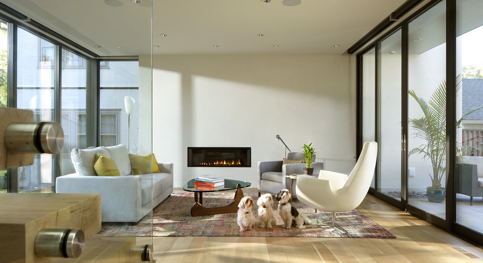 Gas Burning Fireplace, Ceiling Lighting, Chair, Light Hardwood Floor, Staircase, Wood Tread, and Glass Railing  Sheridan Residence by Peterssen/Keller Architecture
