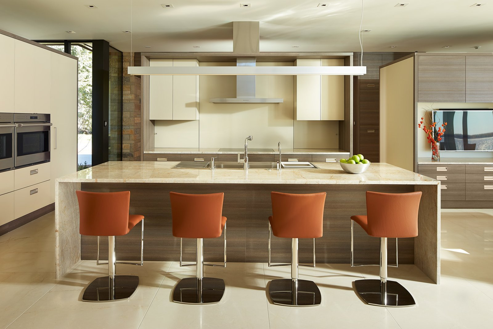 Kitchen, Wall Oven, Marble Counter, Wood Cabinet, Cooktops, White Cabinet, Drop In Sink, and Range Hood  Shoreline Residence by PKA Architecture
