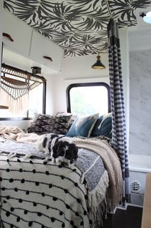 One of their dogs, Cudi, blends in with textiles that overflow on the bed in their RV.