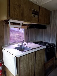 The RV's kitchen space before they stripped away the old wallpaper and updated the cabinetry.