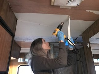 A Portland Couple Renovate a 1982 RV, Turning It Into Their New Home - Photo 4 of 12 - Kamarul removing wallpaper from the ceiling.