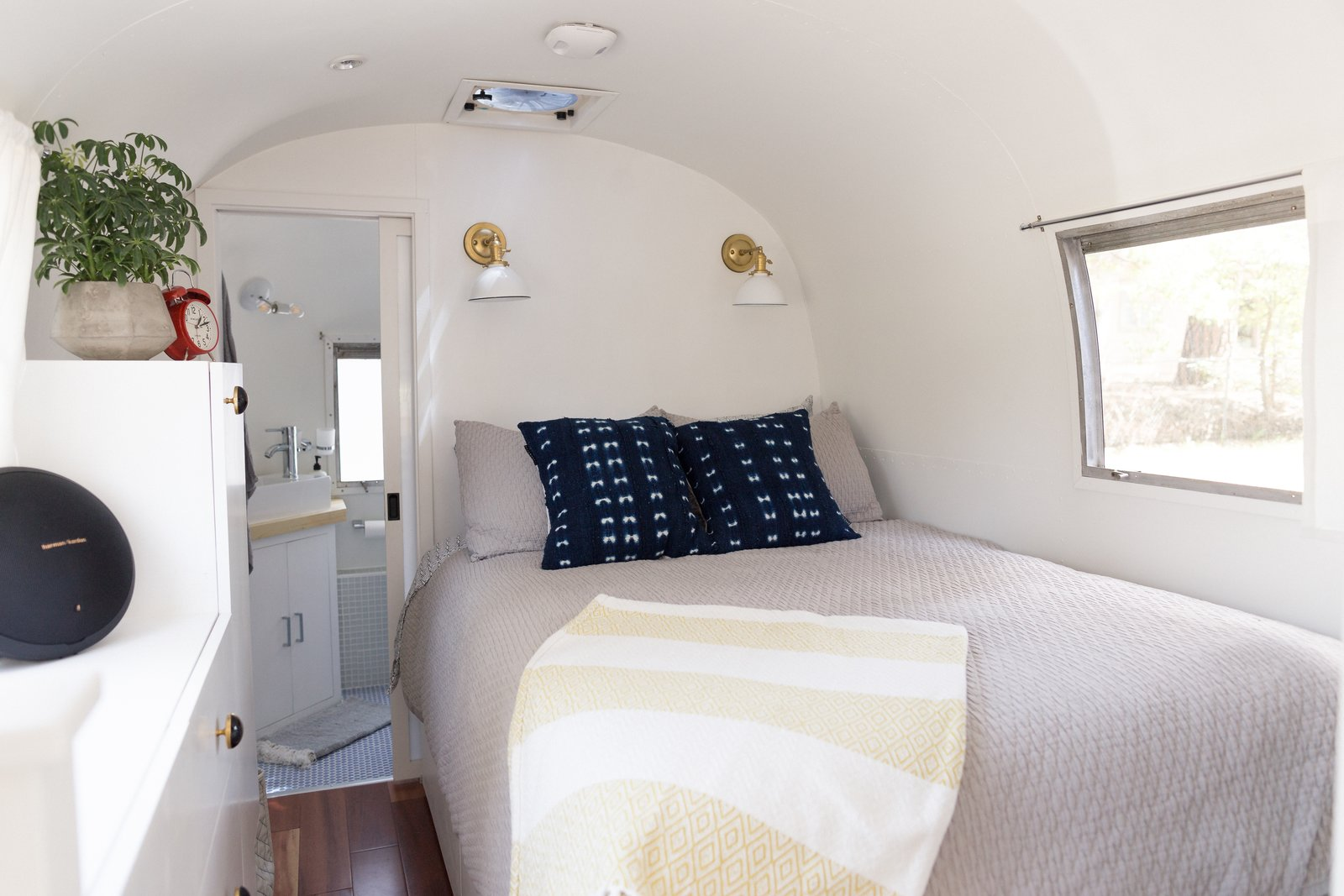 Bedroom, Wall Lighting, Bed, Dresser, and Medium Hardwood Floor  Photo 13 of 25 in See How an Oregon Couple Renovated Their 1966 Airstream