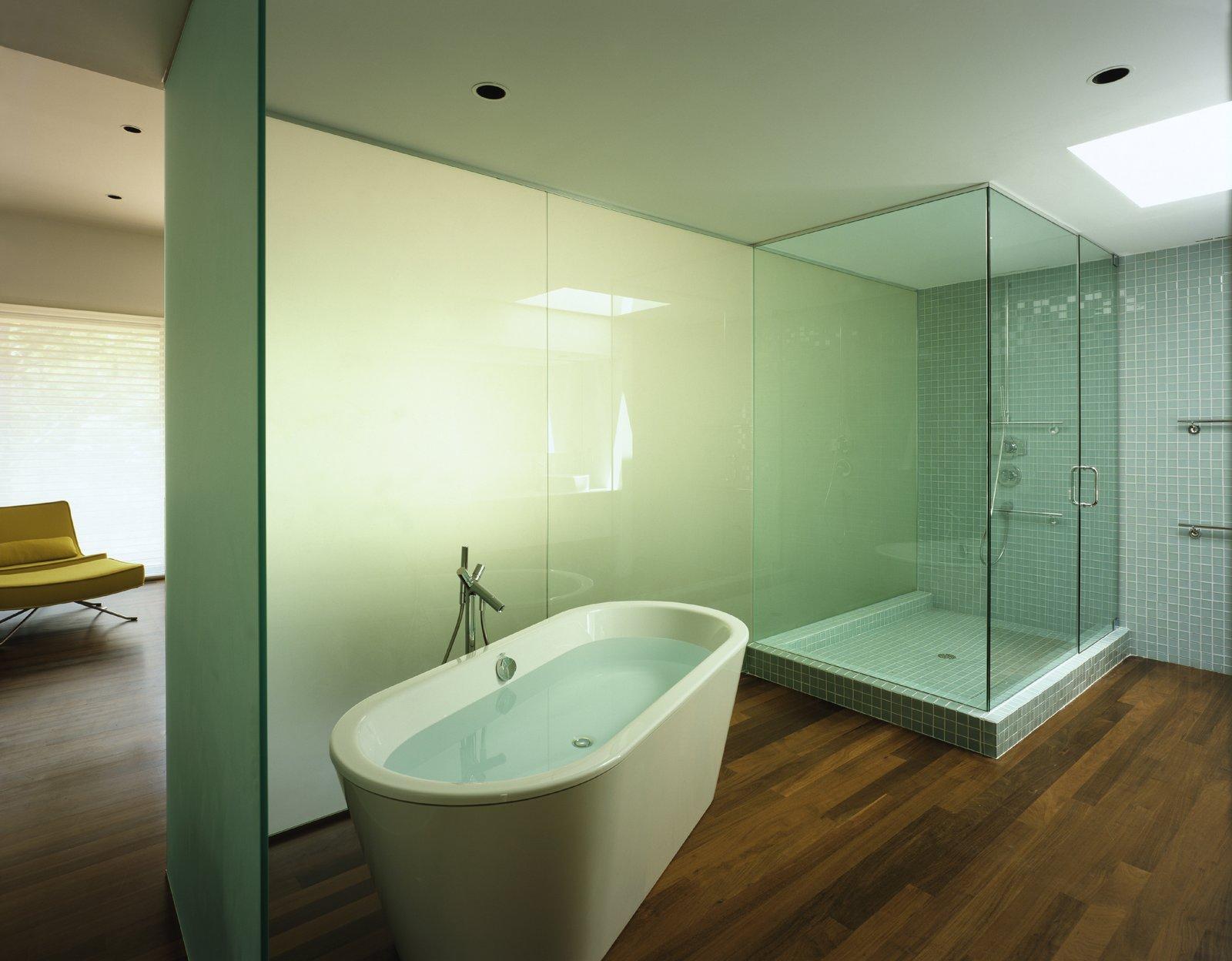 Bath Room, Soaking Tub, Medium Hardwood Floor, Freestanding Tub, Enclosed Shower, Glass Tile Wall, Corner Shower, and Recessed Lighting  Sagaponac House by Hariri & Hariri Architecture