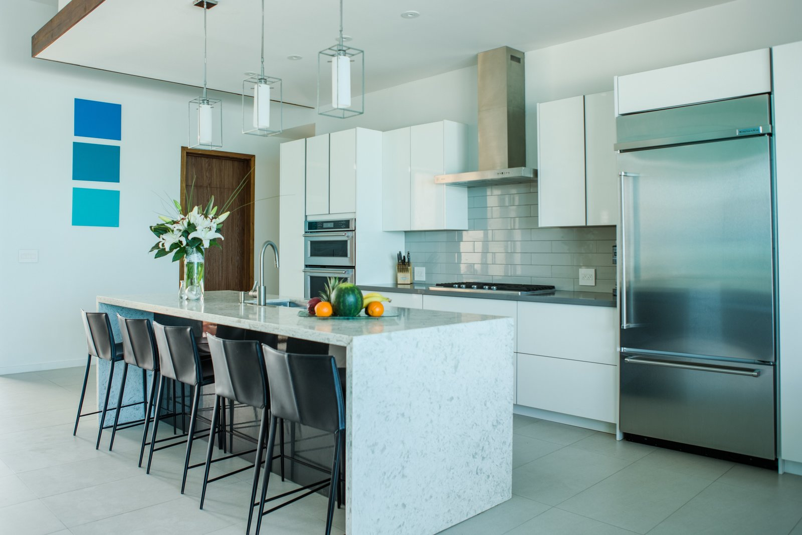 Kitchen, White Cabinet, Subway Tile Backsplashe, Porcelain Tile Floor, Pendant Lighting, Refrigerator, Cooktops, Marble Counter, and Drop In Sink  Tip of the Tail Villa