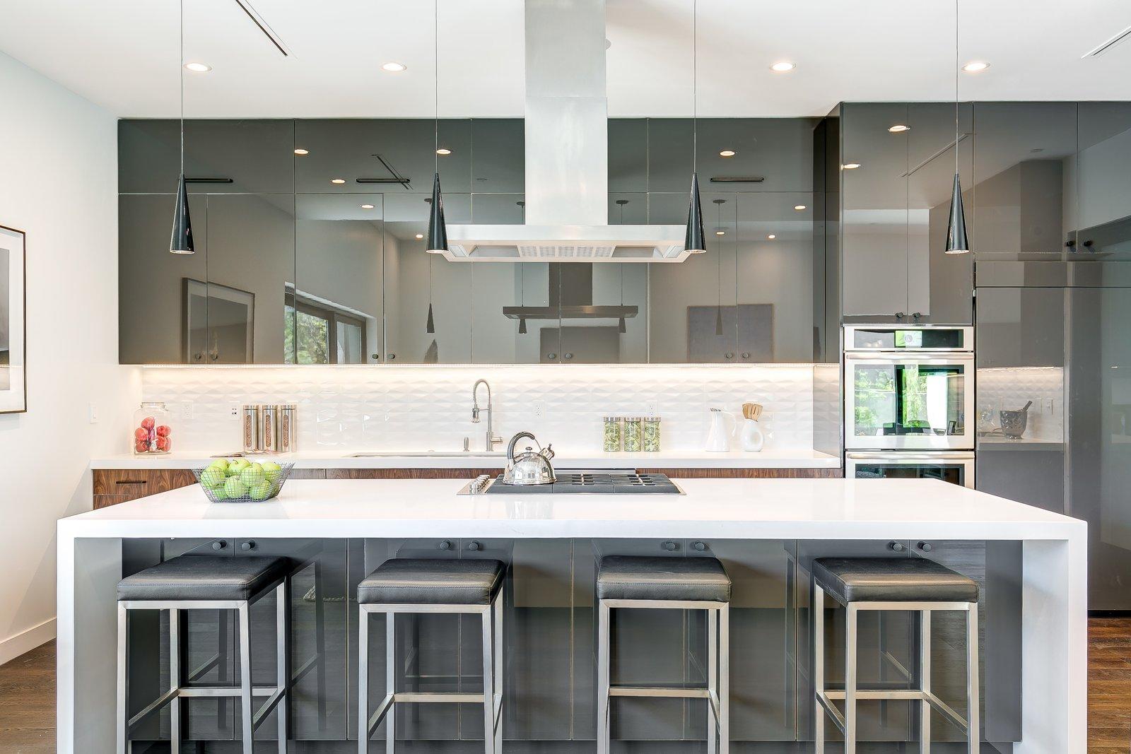 Kitchen, Engineered Quartz Counter, Medium Hardwood Floor, Pendant Lighting, Refrigerator, Wall Oven, Ceiling Lighting, Drop In Sink, and Cooktops  2701 Armacost