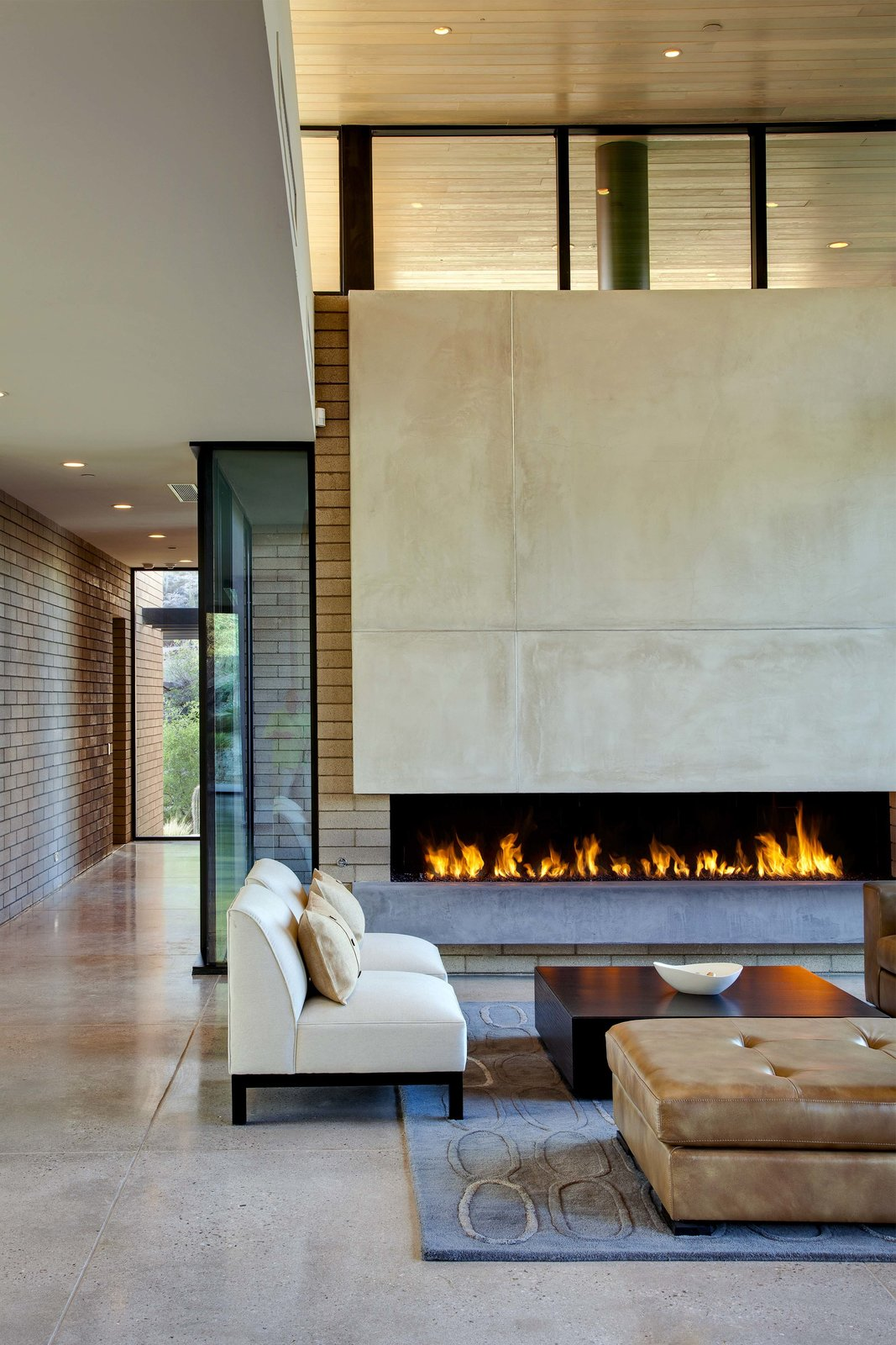 Living Room, Chair, Sofa, Coffee Tables, Ribbon Fireplace, Concrete Floor, and Gas Burning Fireplace  Desert Mountain Home by Kevin B Howard Architects