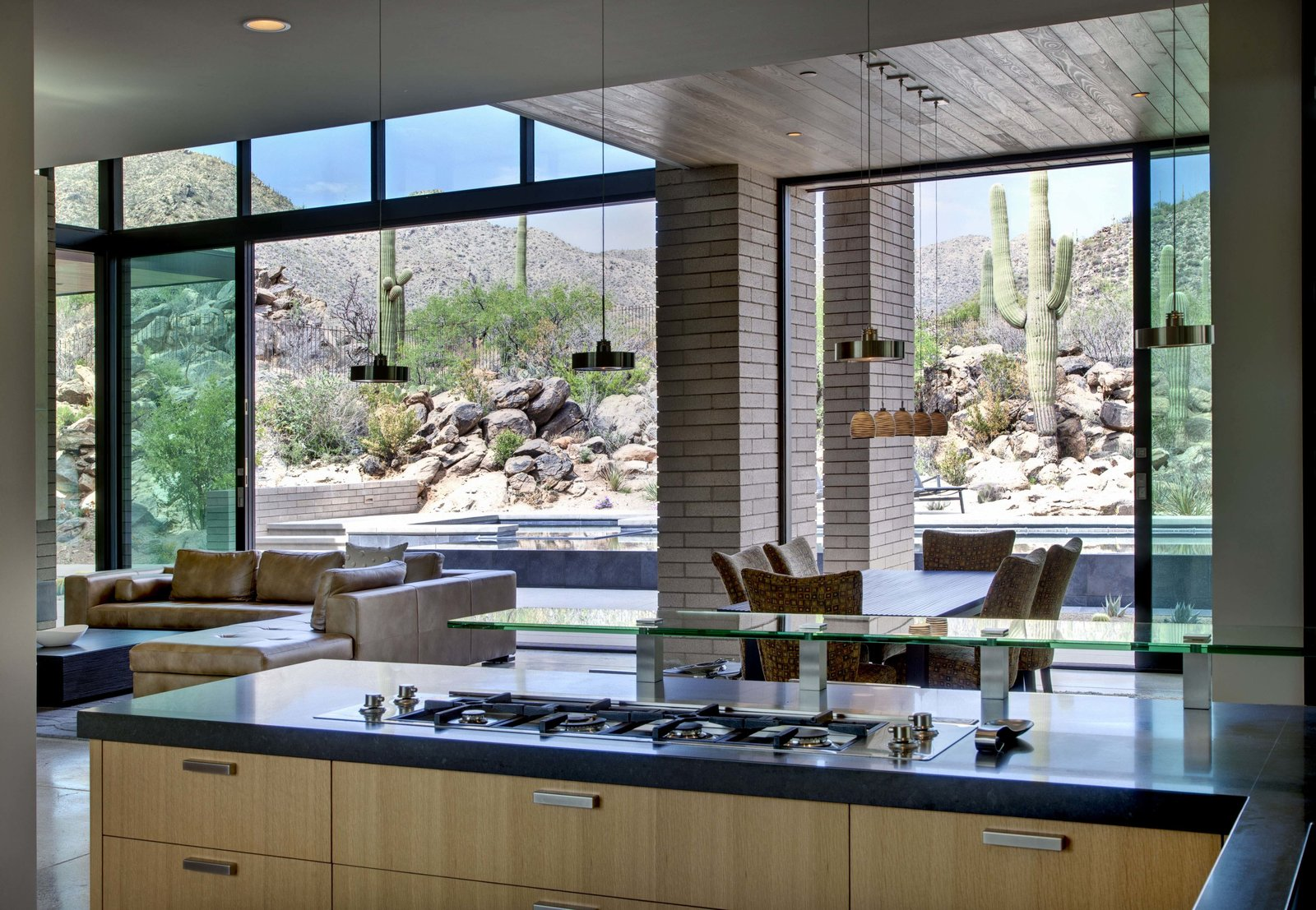 Kitchen, Engineered Quartz Counter, Wood Cabinet, Concrete Floor, Glass Tile Backsplashe, Stone Counter, Pendant Lighting, Recessed Lighting, Ceiling Lighting, and Cooktops  Desert Mountain Home by Kevin B Howard Architects