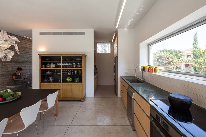 Kitchen, Marble Counter, Ceramic Tile Backsplashe, Concrete Floor, Wood Cabinet, Track Lighting, Ceiling Lighting, Pendant Lighting, Dishwasher, and Cooktops  Urban Life In The Country