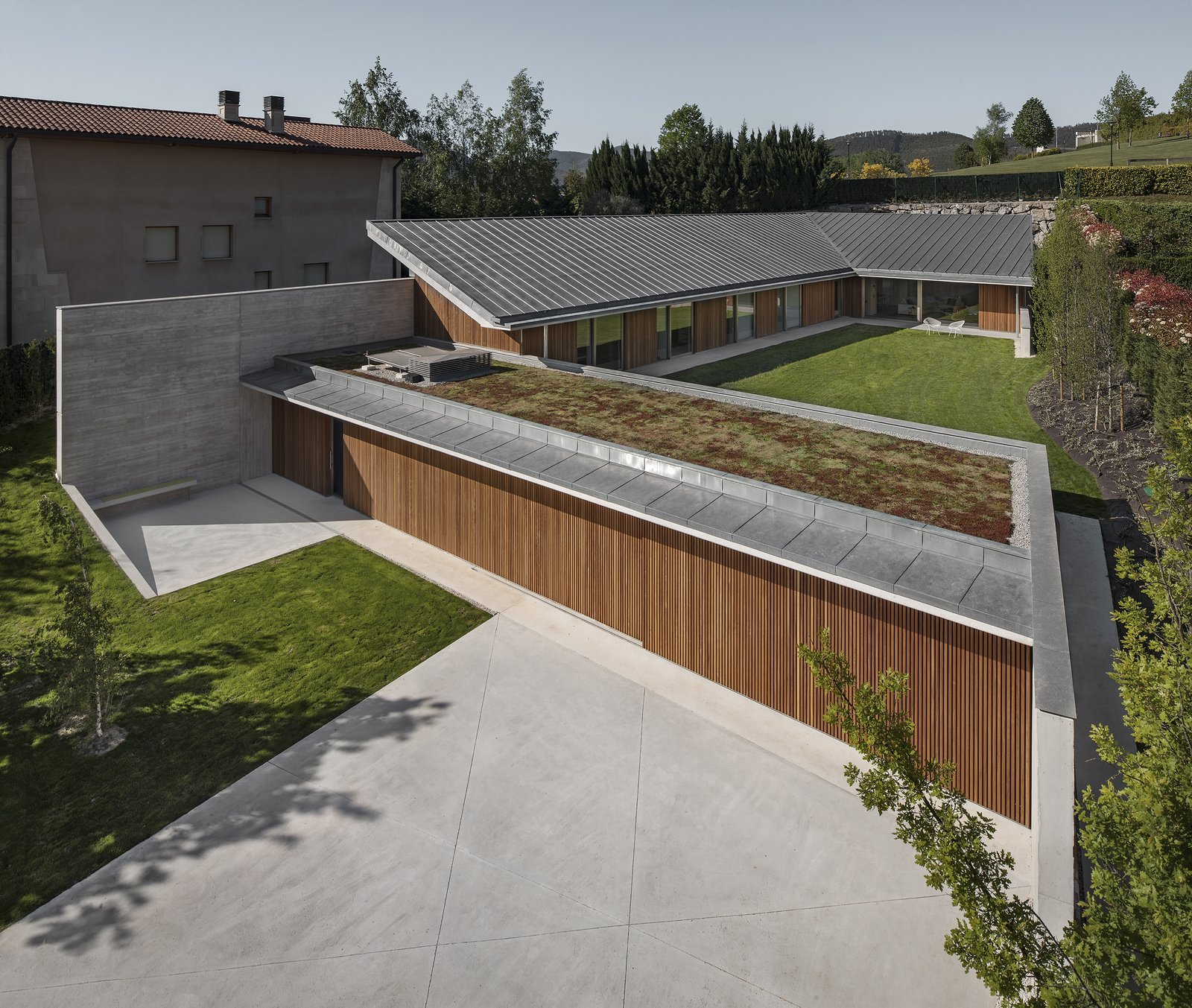 Outdoor, Front Yard, Garden, Rooftop, Trees, Grass, Gardens, Concrete Patio, Porch, Deck, Metal Patio, Porch, Deck, Wood Patio, Porch, Deck, and Wood Fences, Wall  The Öcher House by MLMR Architecture Consultancy