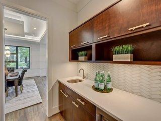 In this butler's pantry, the white glass herringbone backsplash sets off the darker wood cabinetry. Under-cabinet lighting helps reflect light off the glass backsplash.