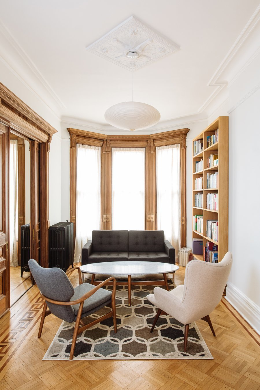 Living Room, Sofa, Chair, Coffee Tables, Bookcase, Shelves, Light Hardwood Floor, Rug Floor, and Pendant Lighting  Photo 3 of 5 in Top 4 Homes of the Week With Floor-to-Ceiling Windows