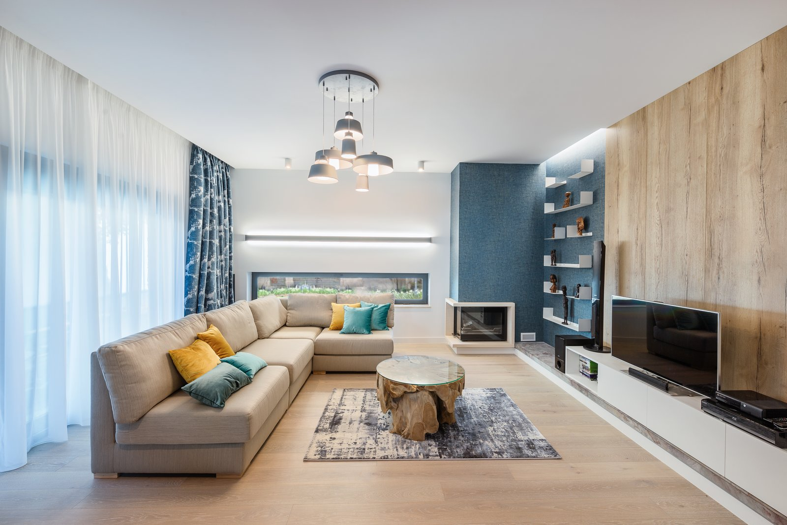 Living Room, Ceiling Lighting, Sofa, Corner Fireplace, Coffee Tables, Bookcase, and Light Hardwood Floor  From Sky to Sea
