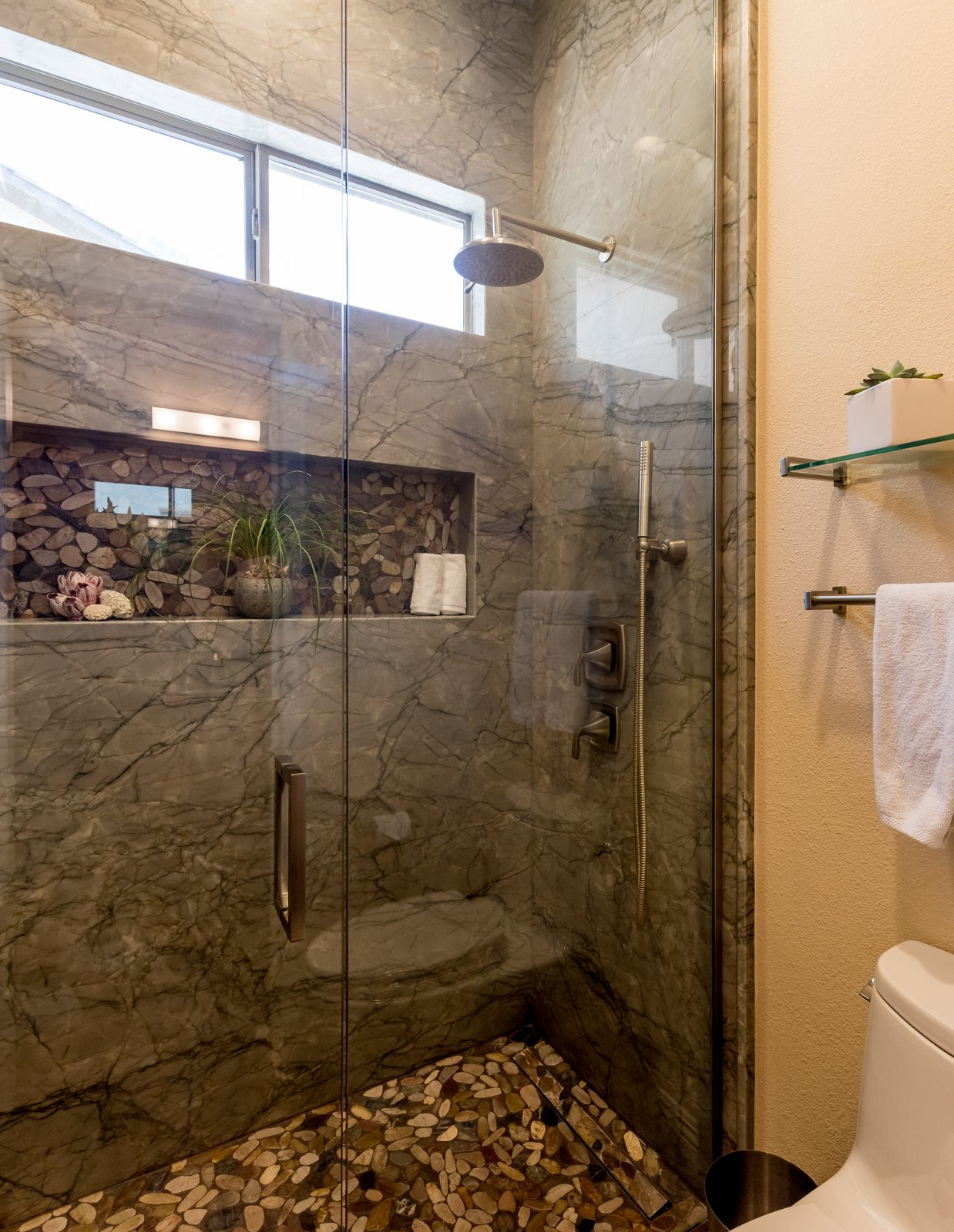 Bath Room, Undermount Sink, Porcelain Tile Floor, Enclosed Shower, Engineered Quartz Counter, Full Shower, Ceiling Lighting, Pendant Lighting, Recessed Lighting, Stone Slab Wall, and One Piece Toilet  Spa Escape
