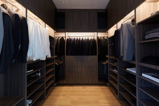 The dramatic design of this master walk-in closet is created with dark wood and warm lighting.
