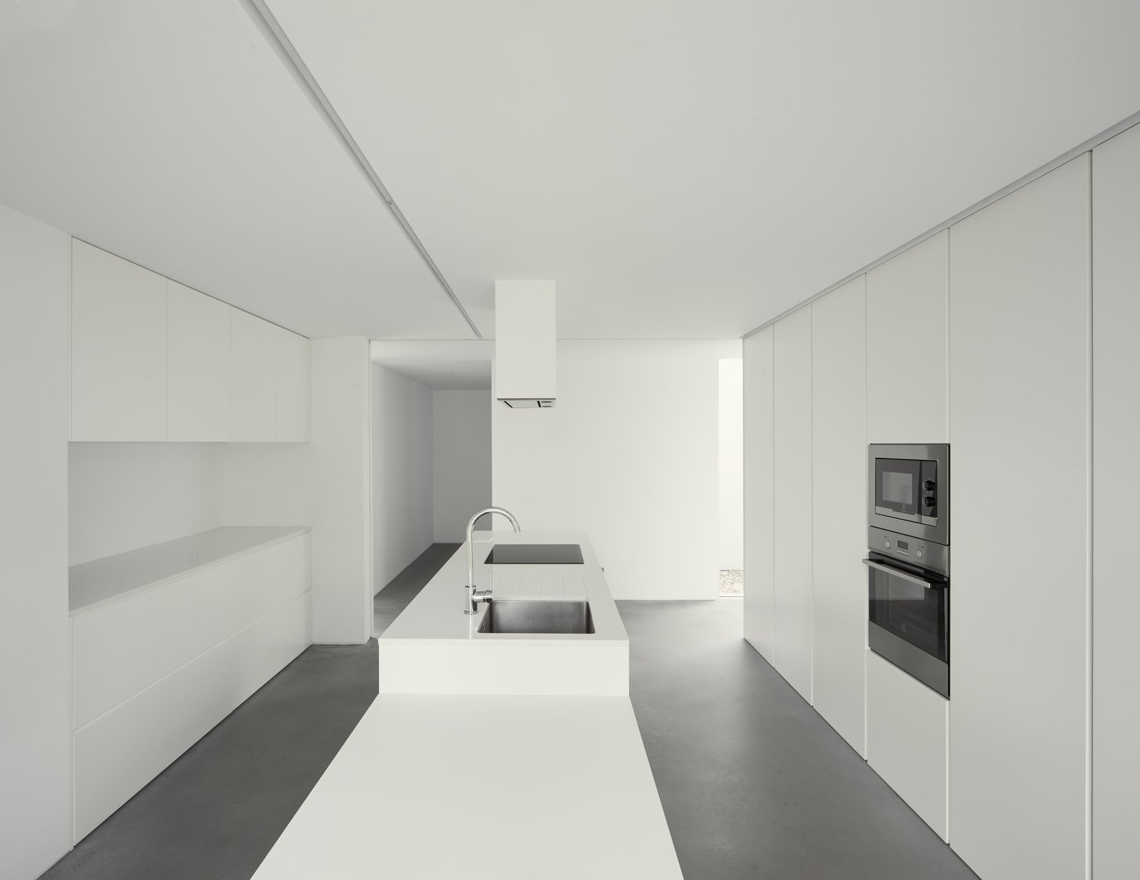 Kitchen, Engineered Quartz Counter, White Cabinet, Concrete Floor, Cooktops, Undermount Sink, and Wall Oven  Fanu House