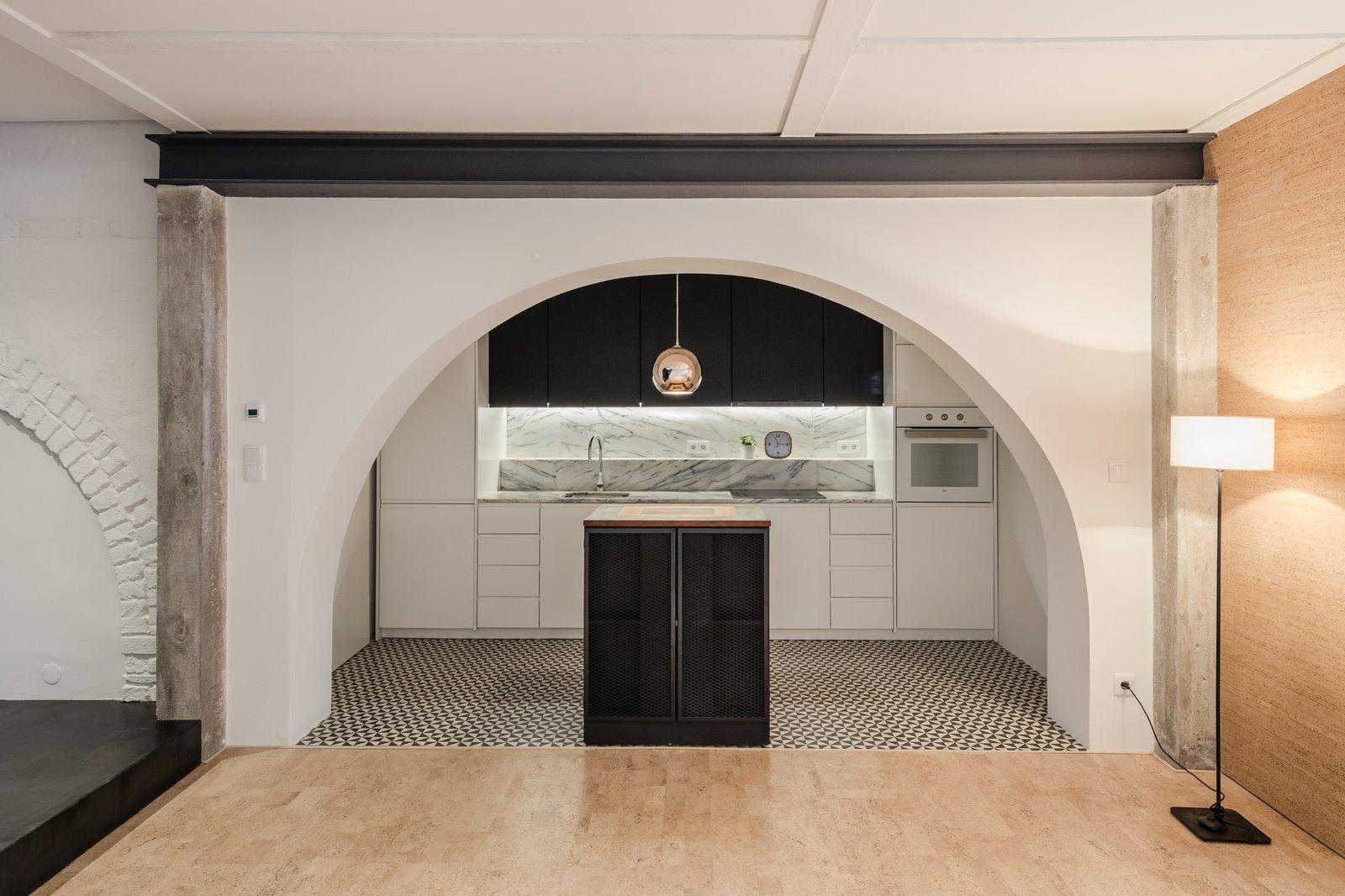 Kitchen, Marble Counter, White Cabinet, Ceramic Tile Floor, Wall Oven, Undermount Sink, Marble Backsplashe, and Pendant Lighting  Rua Maria Loft