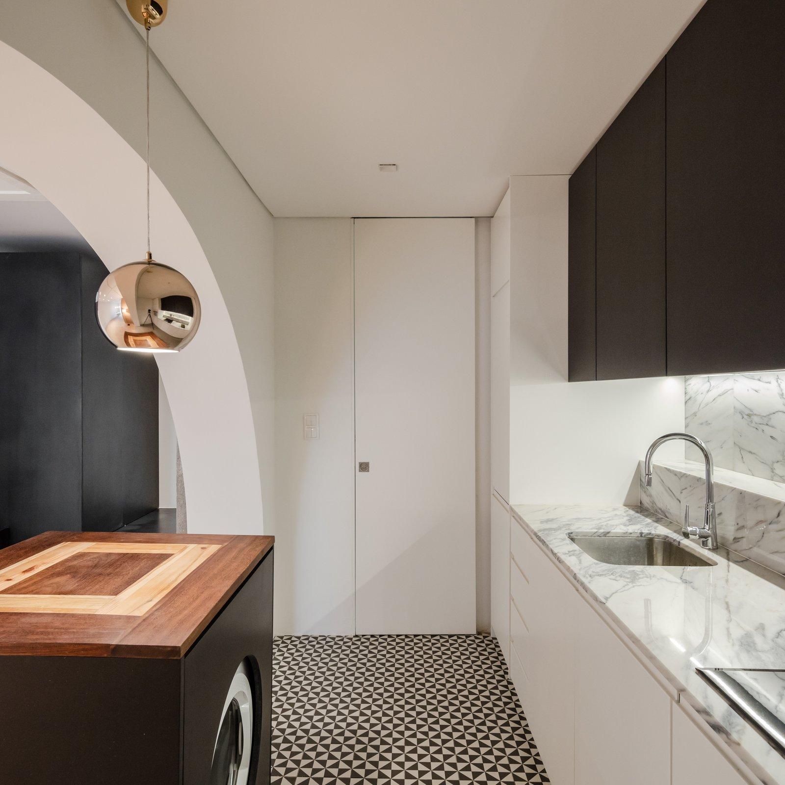 Kitchen, Marble Counter, Wood Cabinet, White Cabinet, Ceramic Tile Floor, Stone Slab Backsplashe, Undermount Sink, and Pendant Lighting  Rua Maria Loft