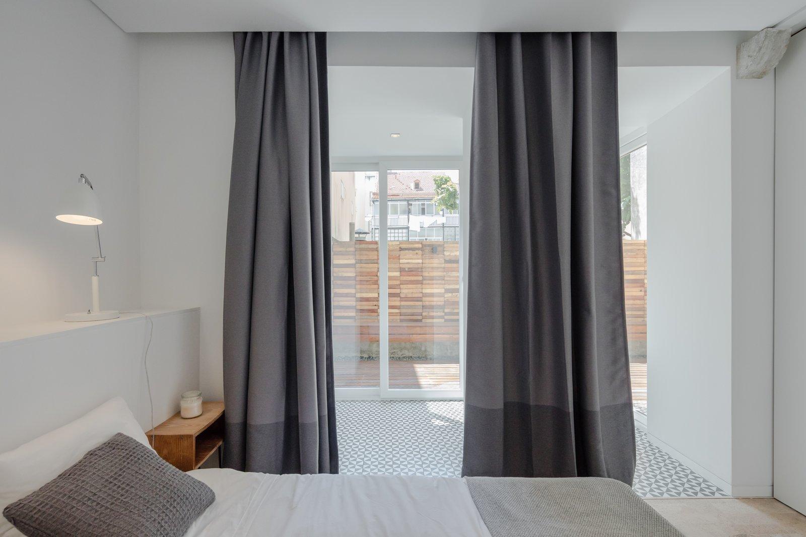 Bedroom, Bed, Night Stands, Cork Floor, Table Lighting, and Ceramic Tile Floor  Rua Maria Loft