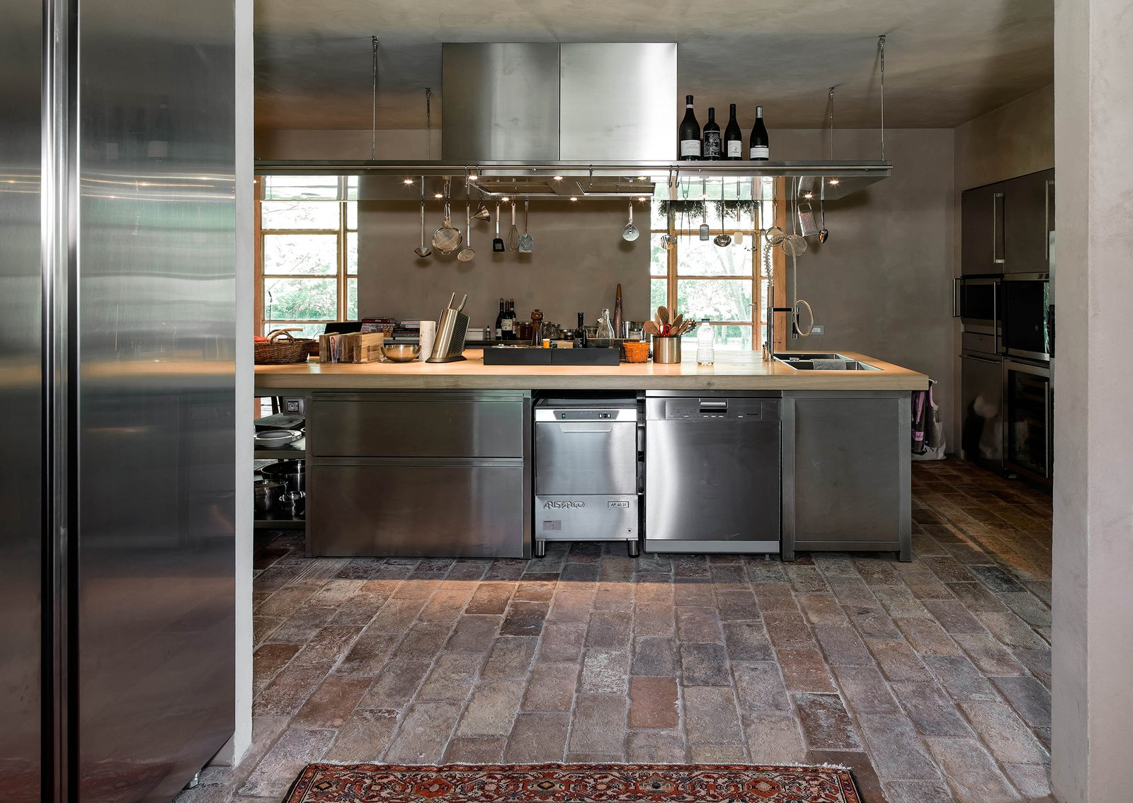 Kitchen, Wood Counter, Metal Cabinet, Laminate Cabinet, Cooktops, and Dishwasher  Country House by zanon architetti associati