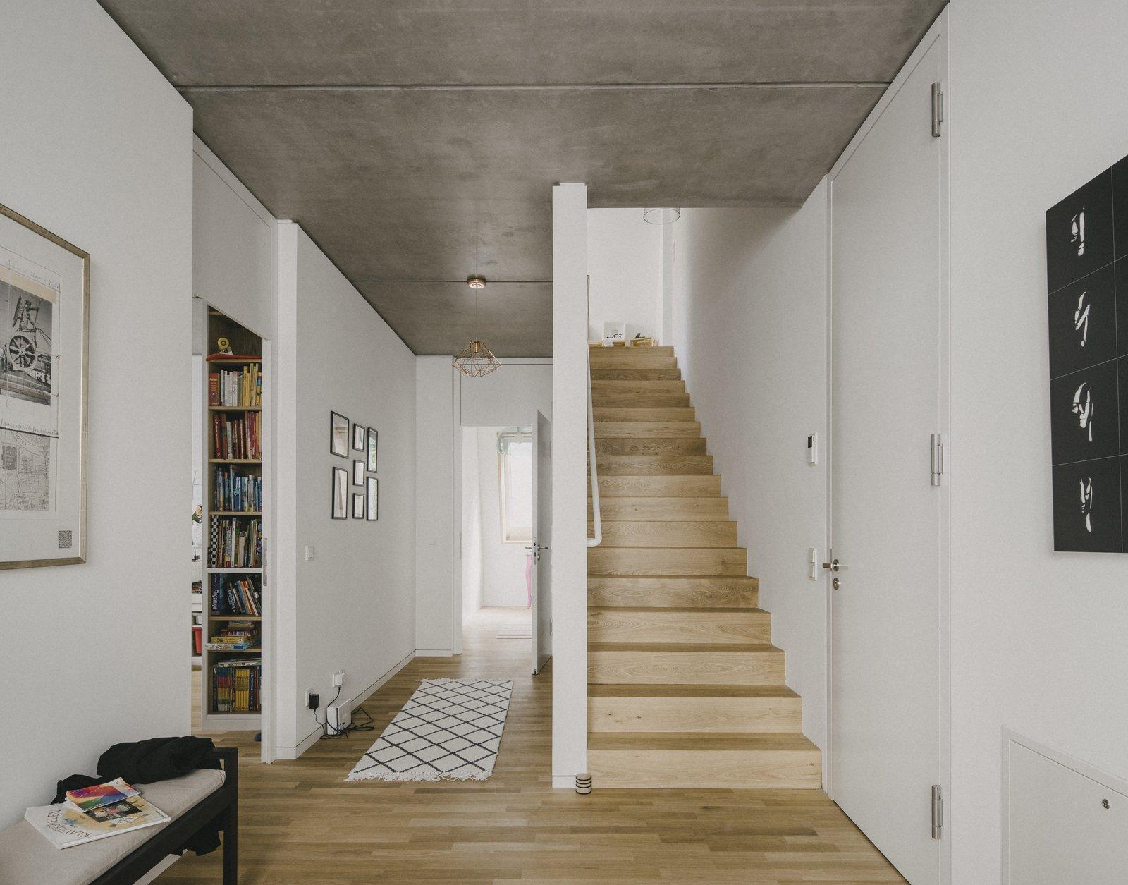 Light Hardwood Floor, Living Room, Bench, Bookcase, Ceiling Lighting, and Concrete Floor  Apartment House Prenzlauer Berg by Barkow Leibinger