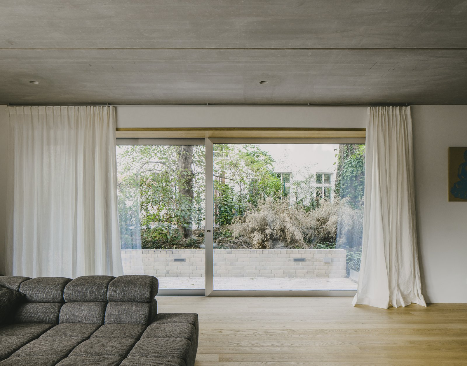 Living Room, Concrete Floor, Light Hardwood Floor, and Sofa  Apartment House Prenzlauer Berg by Barkow Leibinger