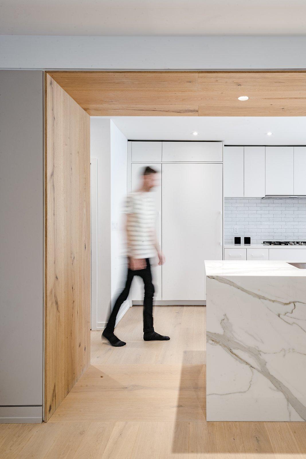 Kitchen, Quartzite Counter, White Cabinet, Subway Tile Backsplashe, Ceiling Lighting, Recessed Lighting, Light Hardwood Floor, Refrigerator, and Undermount Sink  Richview Residence