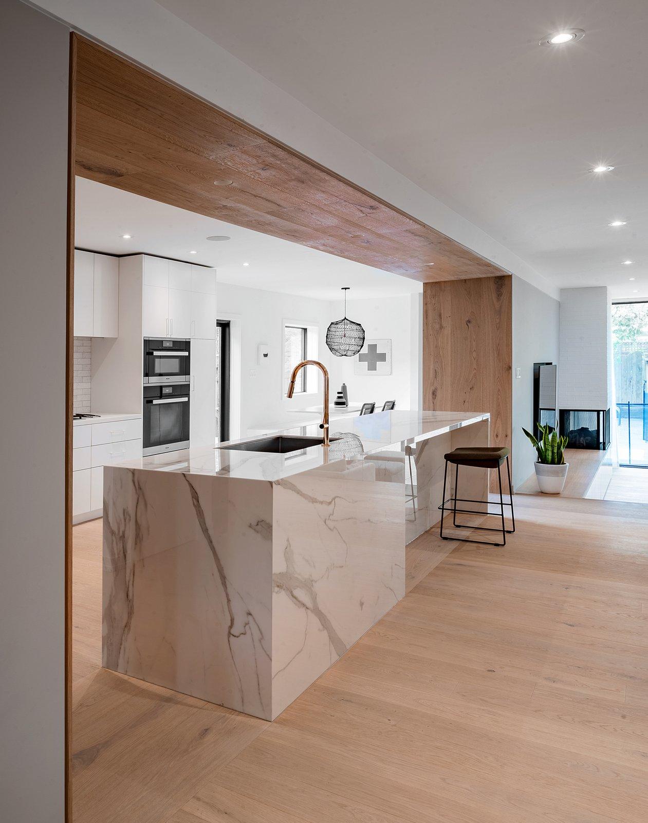 Kitchen, Quartzite Counter, White Cabinet, Light Hardwood Floor, Ceiling Lighting, Subway Tile Backsplashe, Recessed Lighting, Undermount Sink, and Wall Oven  Richview Residence
