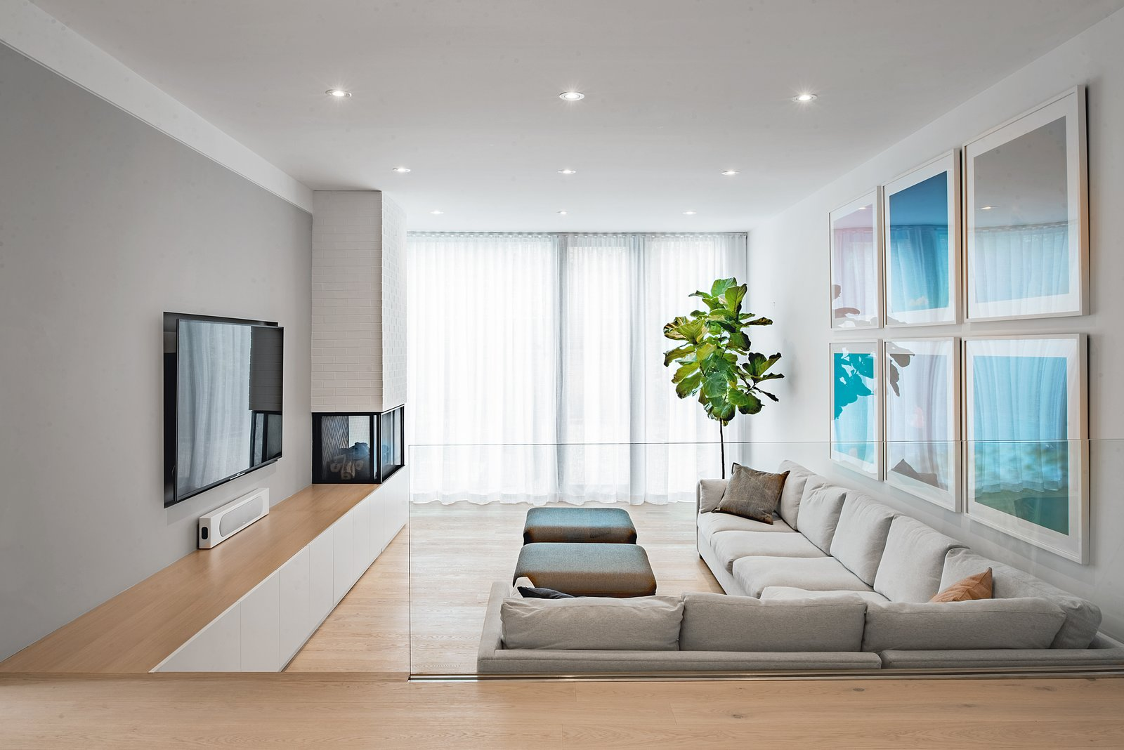 Living Room, Bench, Chair, Sofa, Sectional, Ottomans, Light Hardwood Floor, Ceiling Lighting, Console Tables, Corner Fireplace, and Two-Sided Fireplace  Richview Residence