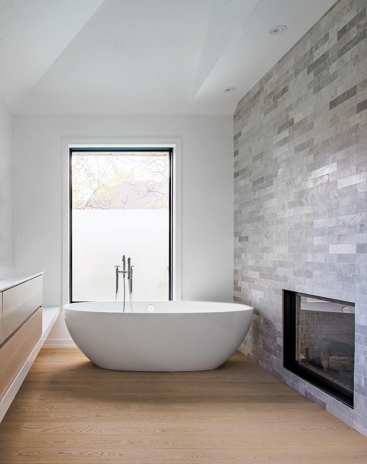 Bath Room, Engineered Quartz Counter, Undermount Sink, Light Hardwood Floor, Freestanding Tub, Ceiling Lighting, Open Shower, Stone Tile Wall, and Soaking Tub  Richview Residence
