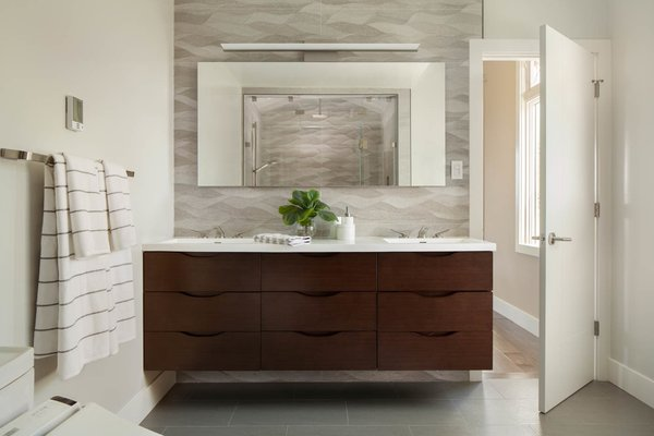 This Los Altos Hills, California bathroom remodel added diffuse LED backlighting, a floating vanity and an accessible, walk-in shower, stylish yet practical additions that improve the value to both homeowner and potential buyer.