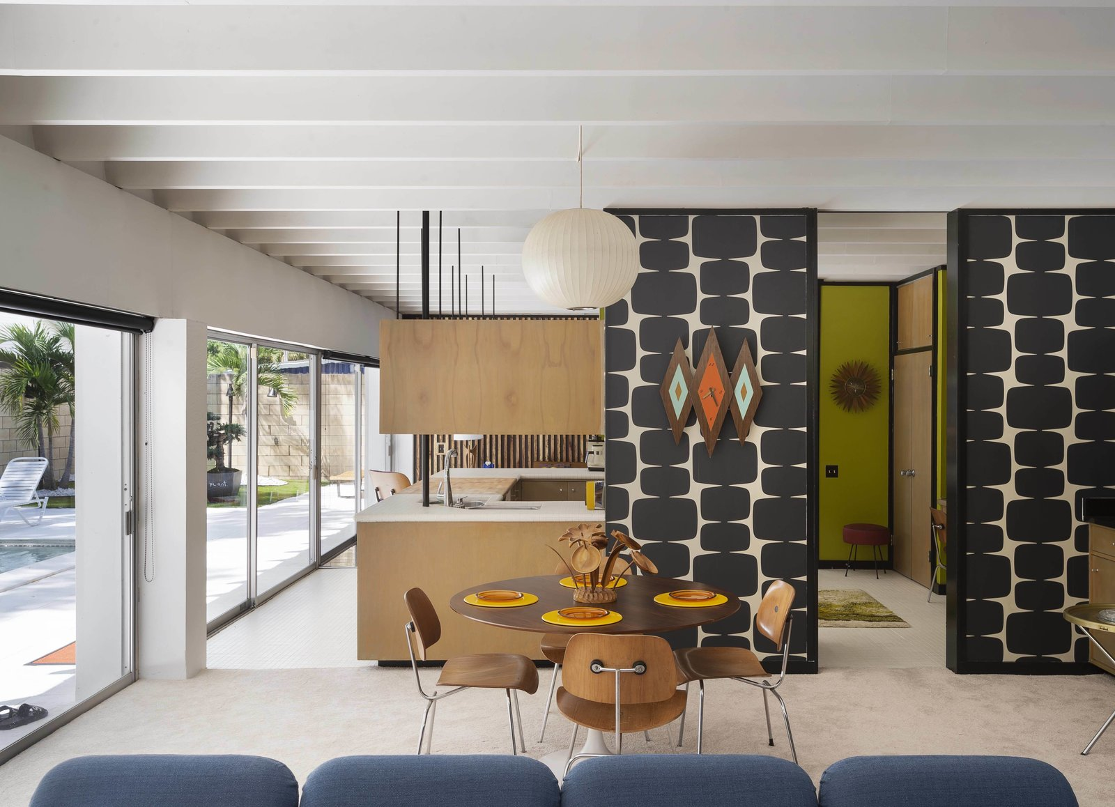 A Herman Miller chicklet sofa (foreground) and a Saarinen by Knoll dining table with Eames' DCM plywood chairs are clearly at home in this authentic midcentury modern abode.
