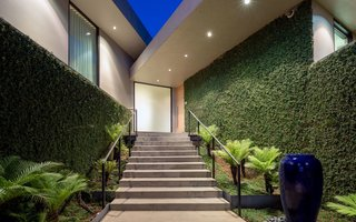 Close to the street, the entrance is protected from prying eyes by angular walls and plenty of foliage.
