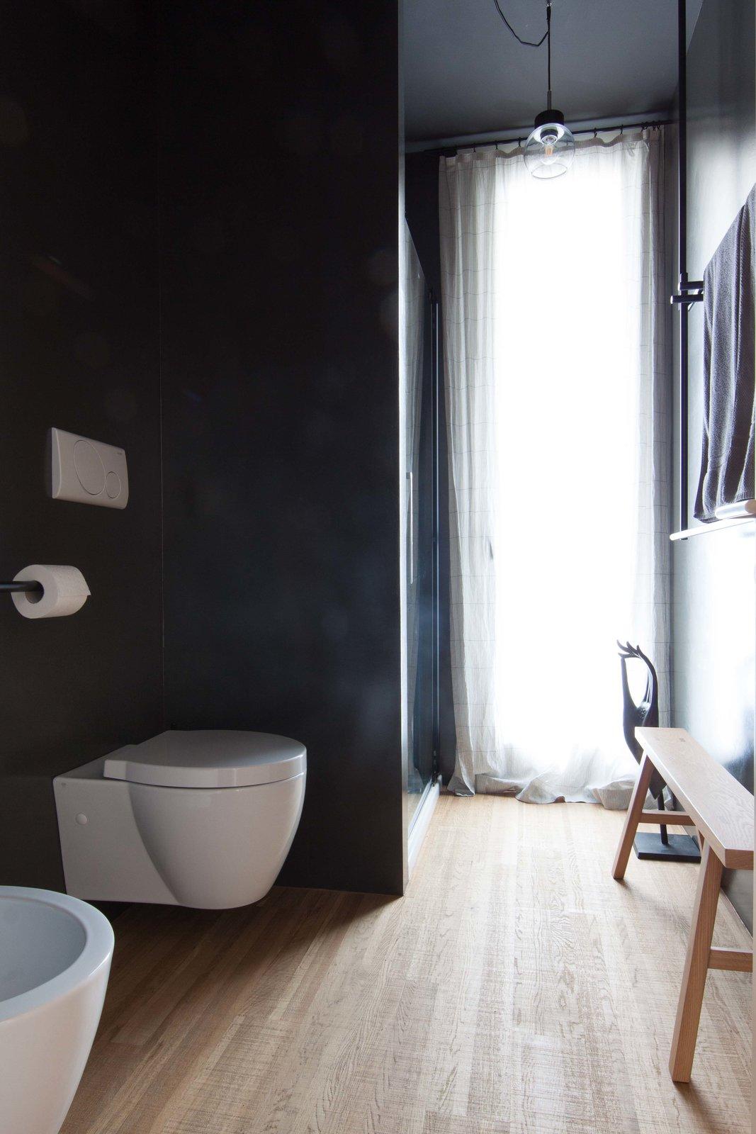 Bath Room, Medium Hardwood Floor, Pendant Lighting, Enclosed Shower, Concrete Wall, and One Piece Toilet  Interior LP by Didonè Comacchio