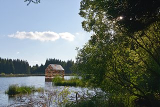 Built in the same dimensions as poet Henry David Thoreau's Walden Pond cabin, this small 13-by-8-foot dwelling is an art installation on France's Lac de Gayme and was constructed out of reclaimed wood and recyclable acrylic glass.