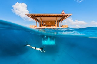 "Off the coast of Tanzania in the Indian Ocean, Manta Resort's ""Underwater Room"" is a three-level suite surrounded by a coral reef. Below water, guests can watch marine life—while on the rooftop deck, they can soak up the sun."