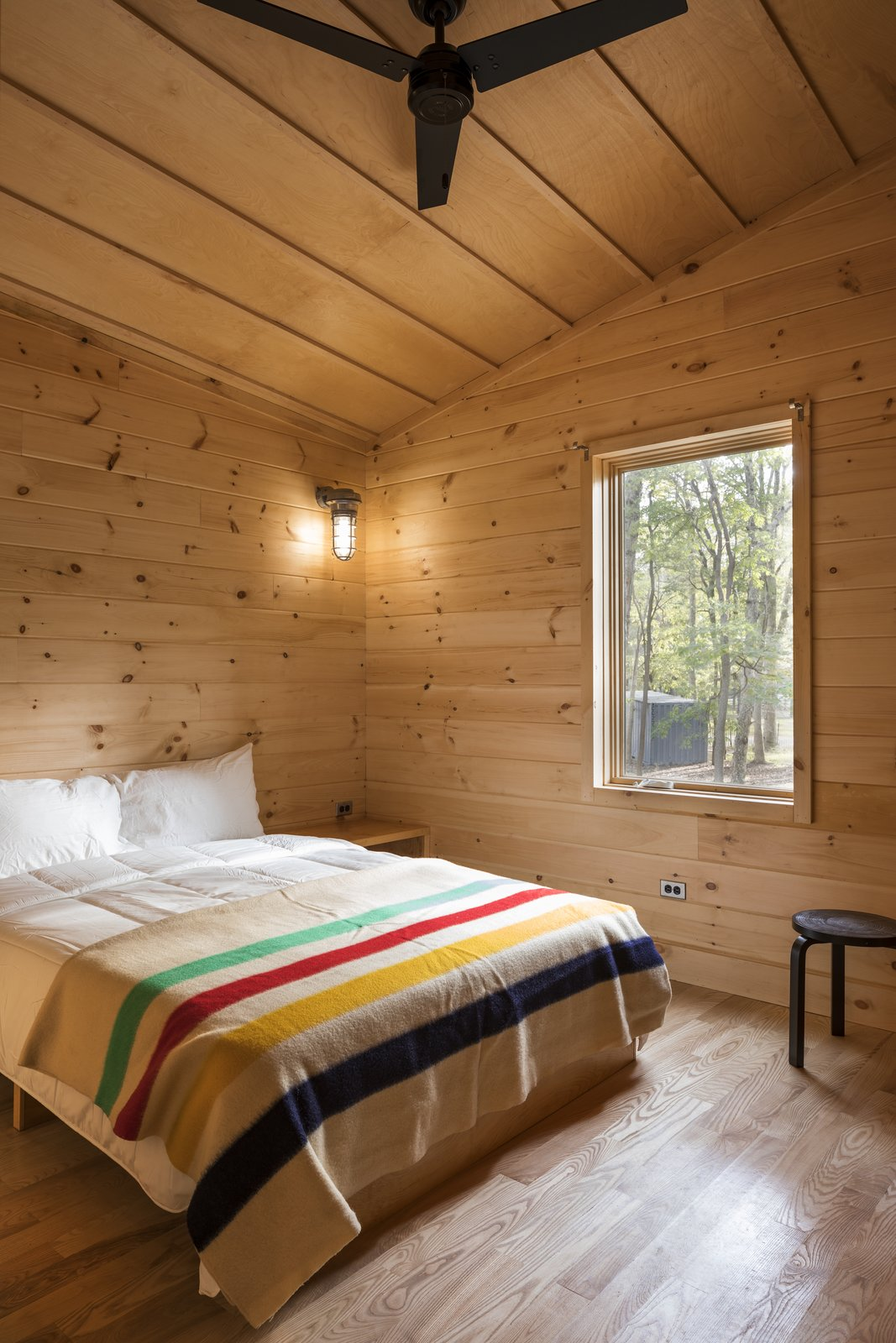 Bedroom, Bed, Night Stands, Wall Lighting, and Light Hardwood Floor  Photo 7 of 7 in A Long Island Campground Gets a Bunch of New Modern Cabins