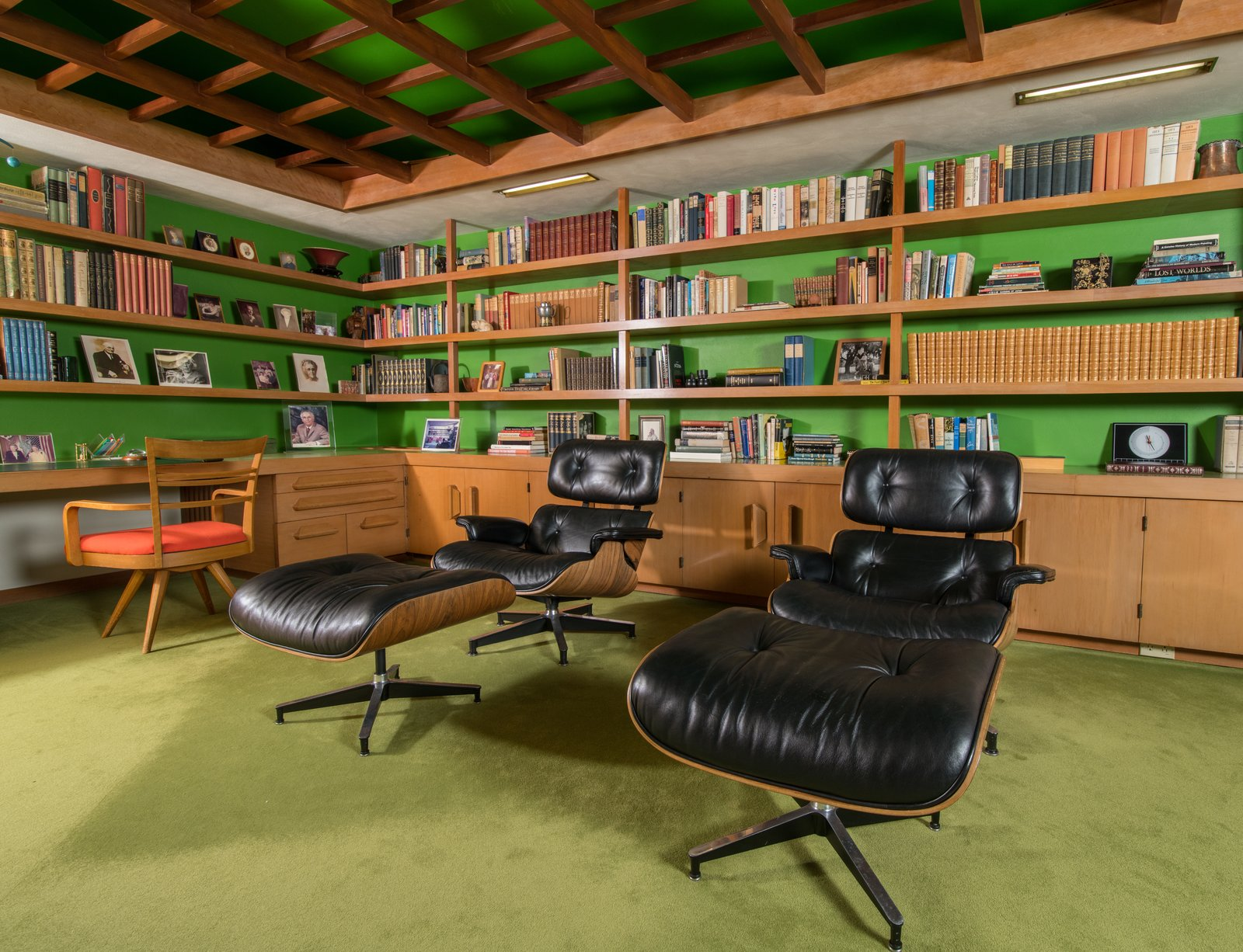 """The rosewood-veneered molded plywood and leather swivel Eames Lounge Chair and Ottoman, which was designed for the furniture company Herman Miller, was intended to have a """"warm receptive look of a well-used first baseman's mitt,"""" which was achieved by buttoning the leather to create creasing in the black hide."""