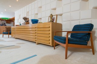Midcentury modern lounge chairs flank the Herman Miller buffet table that Dow designed himself.