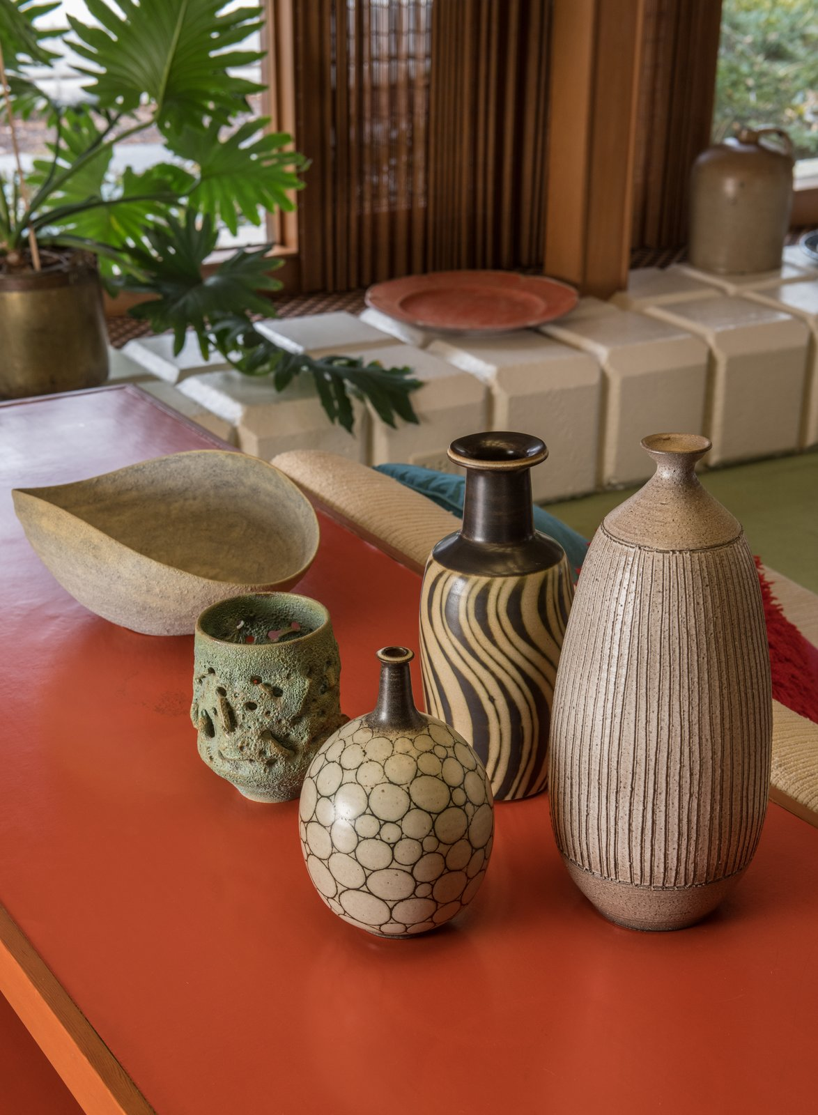 """""""Each element contributes its own part to the entire whole,"""" says Quinn. """"Going through structure, integrating iconic pieces, it was about the feel.""""  A mix of McIntosh and Natzler ceramics is displayed in the living room."""