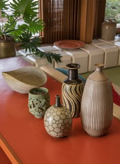 """Each element contributes its own part to the entire whole,"" says Quinn. ""Going through structure, integrating iconic pieces, it was about the feel.""  A mix of McIntosh and the Natzlers ceramics are displayed in the living room."
