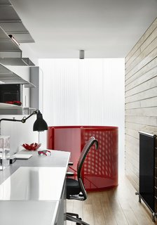The home office is paneled in wood with perforated steel shelving.